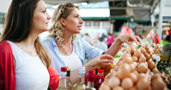 Junge Frauen kaufen auf dem Markt gesundes Gemüse und Obst