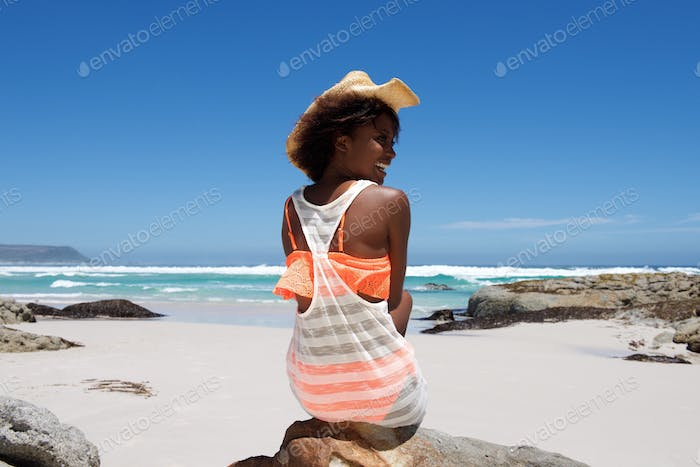 Cheerful young woman with hat sitting by the beach