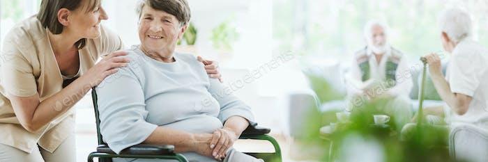 Glückliche Betreuer mit älteren Patienten auf dem Rollstuhl