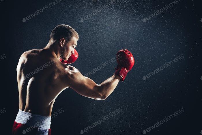 Mann Boxen mit roten Handschuhen an den Händen im Regen.