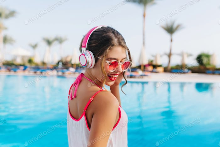 Excited brunette girl with tanned skin listening favoring music while sunbathing by the open-air poo