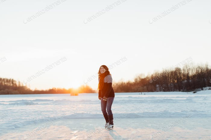 Happy female skater ice skating on a frozen lake