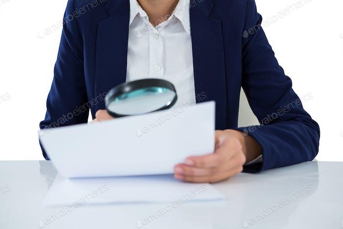 Mujer de negocios mirando el documento a través de la lupa