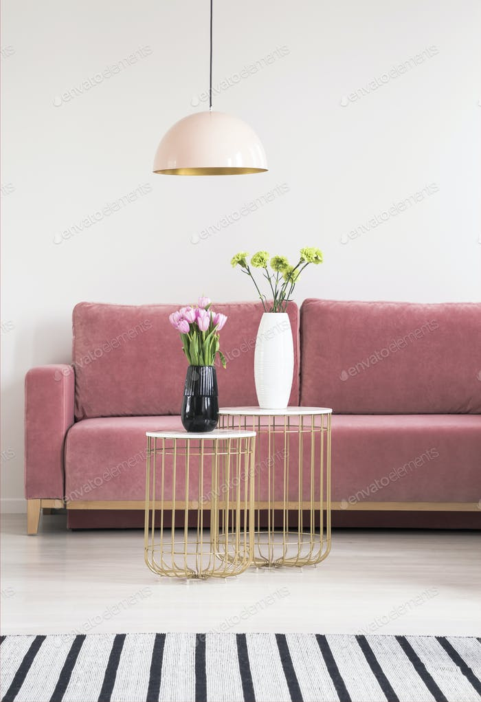 Golden small tables with flowers, pink couch and chandelier in a