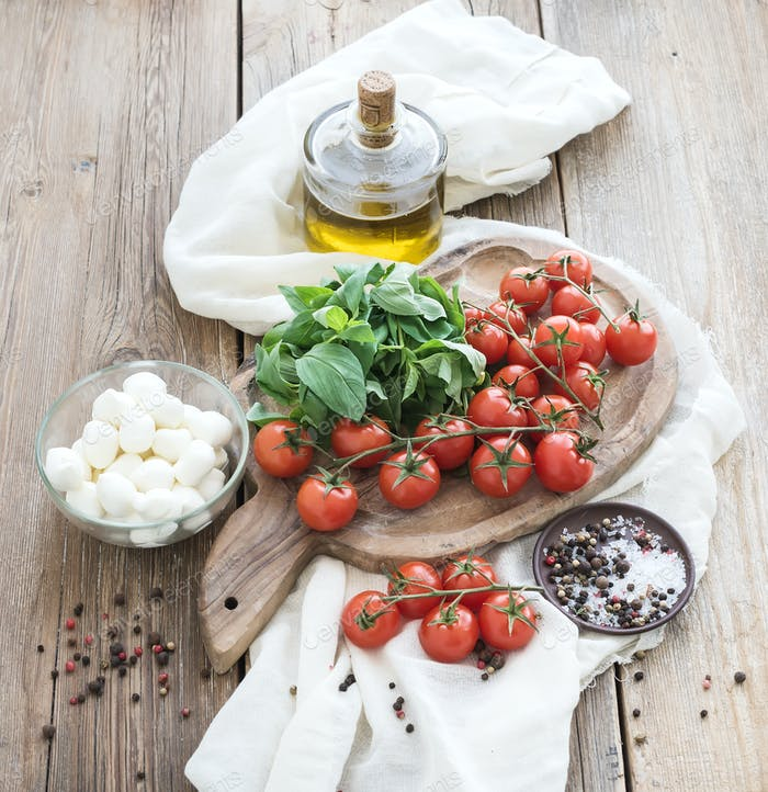 Basil, cherry-tomatoes, mozarella, olive oil, salt, spices on rustic chopping board