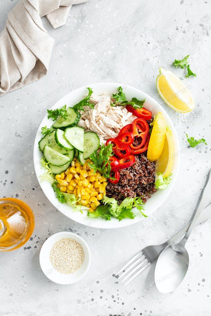 Fiambrera de pollo con hojas frescas de ensalada, maíz, pepino, pimiento dulce y quinoa