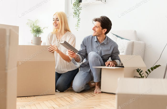 Young Spouses Unpacking Moving Boxes In New House After Relocation