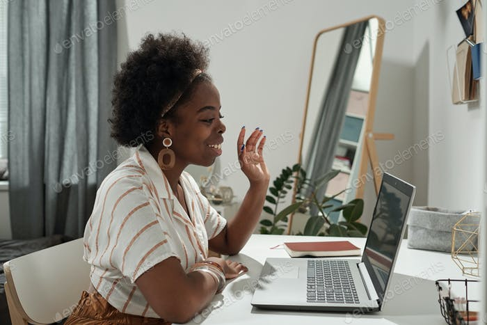 Young employee waving hand to someone on laptop screen