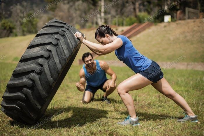 Fit Frau Umdrehen eines Reifens während Trainer jubeln während Hinderniskurs