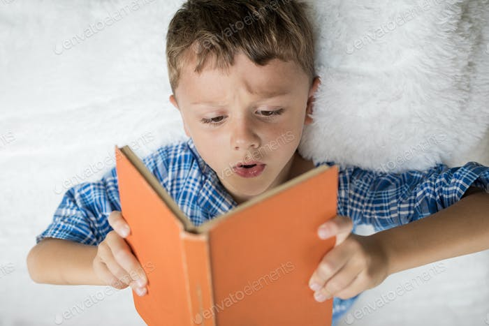 little boy is lying on the bed and reading a book