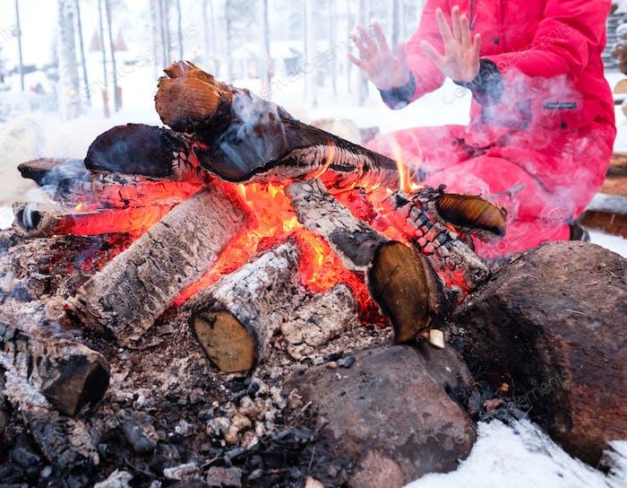 Woman near bonfire in winter landscape