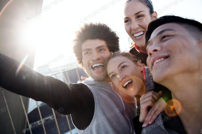 Fit und sportlich Team mit Handy in der Stadt.