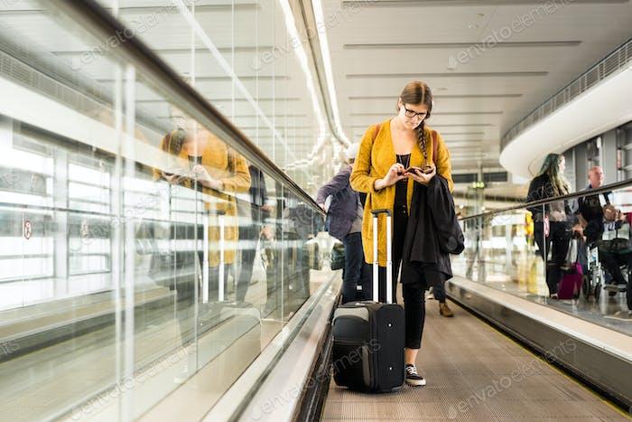 Mujer de negocios que usa el teléfono inteligente en movimiento pasarela en el aeropuerto