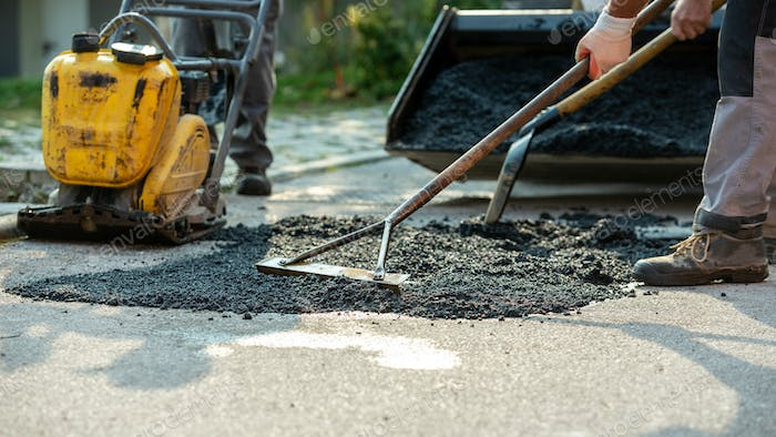 Low angle view of two workers arranging fresh asphalt mix with rakes and shovel