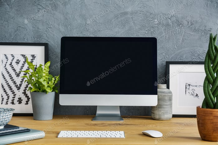 Close-up of a black, empty screen, plants, keyboard and painting