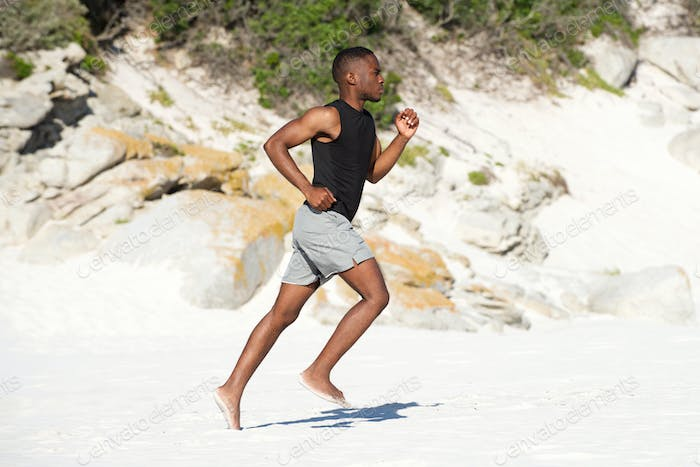 Healthy active young african man running on the beach