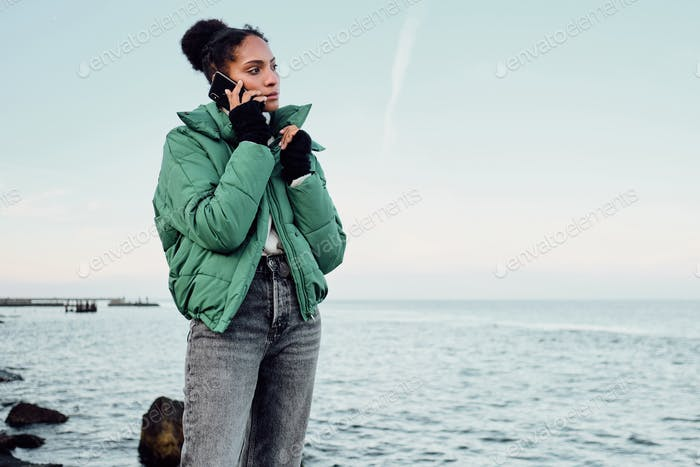 Beautiful casual African American girl in down jacket thoughtfully talking on cellphone by the sea