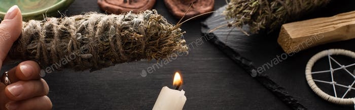 Shaman Holding Smudge Stick And Candle Near Witchcraft on Black Wooden Surface, Panoramic Shot