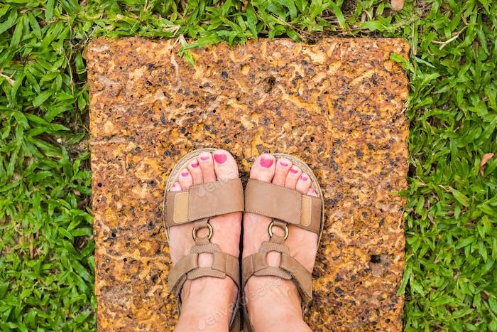 Feet selfie from upper view of a woman traveler in sandal