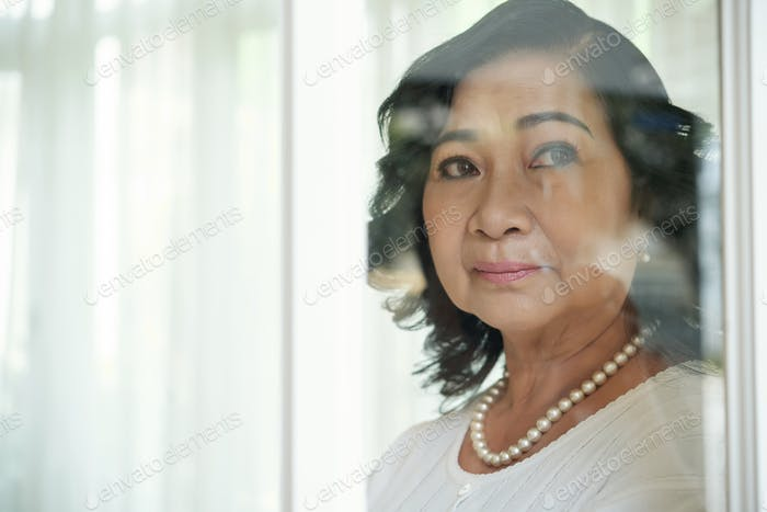 Thoughtful Retired Asian Woman