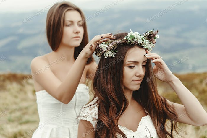 stylish bridesmaid helping gorgeous bride preparing