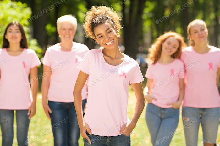 Breast Cancer Volunteer Standing In Front Diverse Ladies In Park