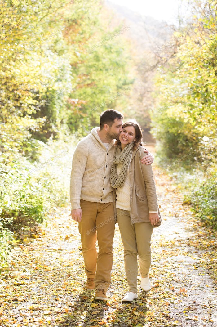 Beautiful young couple on a walk in colorful autumn nature.