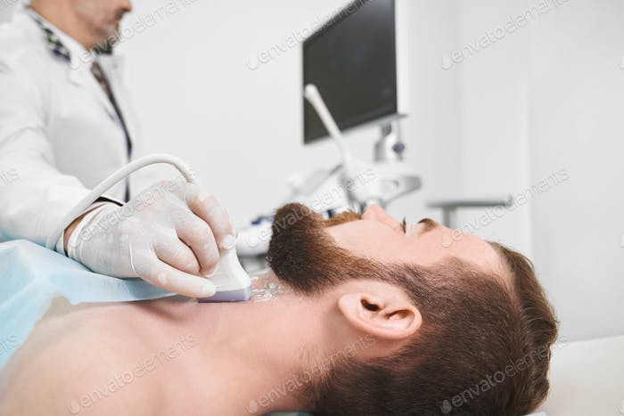 Doctor using ultrasound probe for lymph node diagnosis