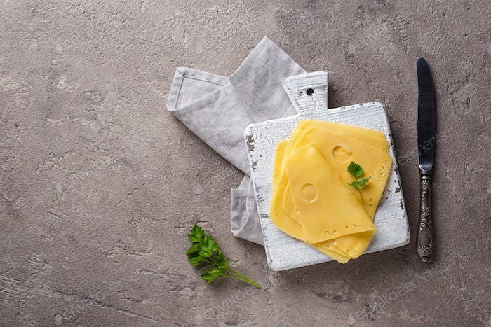 Sliced cheese on cutting board