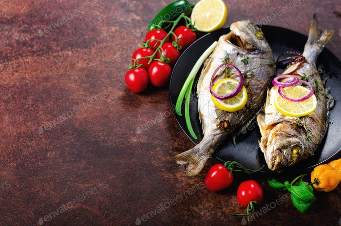 Cooked baked grilled fish, dorado, sea bream with lemon, herbs, vegetables and spices on rustic