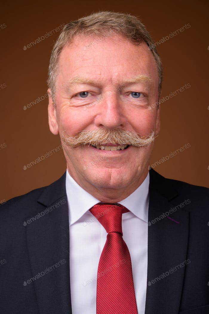 Face of happy senior businessman wearing suit and tie while smiling
