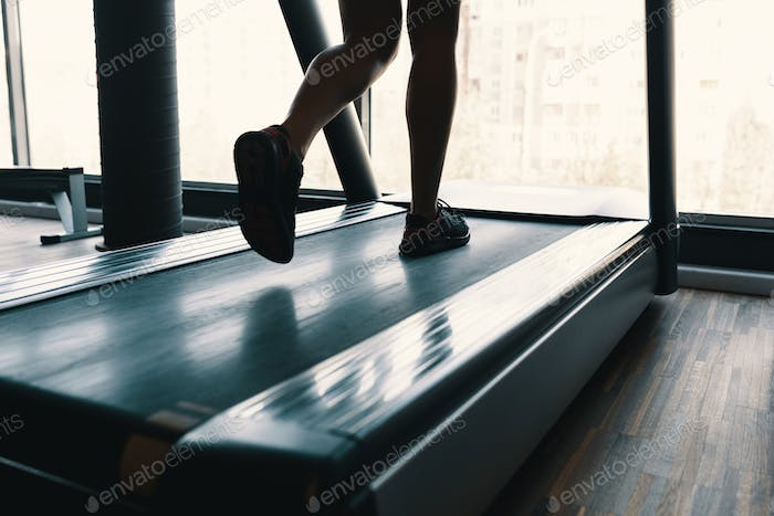 Early morning sport, female legs running on the gym treadmill ea