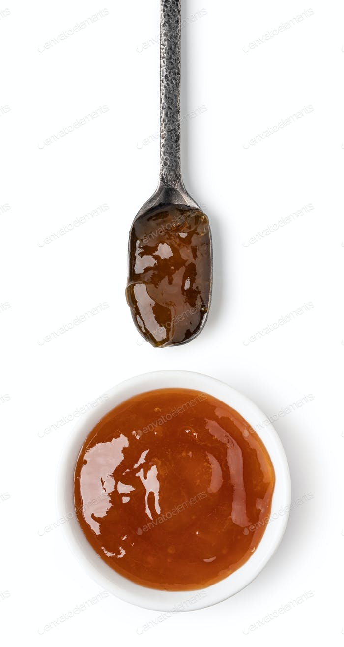 Small glass bowl and spoon of apricot jam