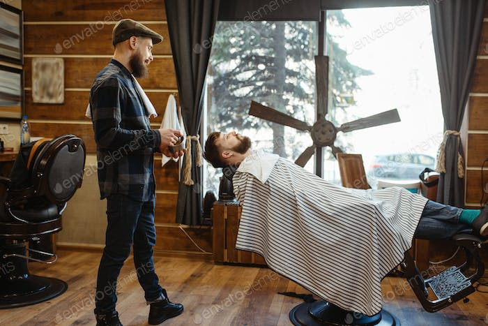 Barber in hat and bearded customer, beard cutting