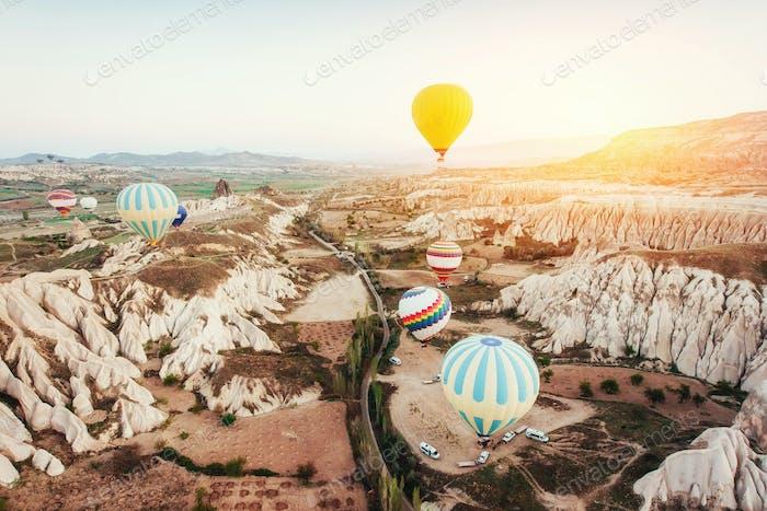 Hot air balloon flying over rock landscape at Turkey. Cappadocia