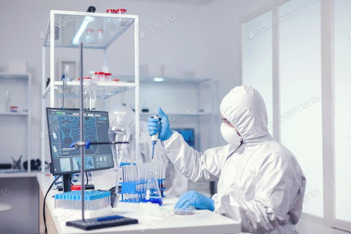 Researcher testing liquid sample uses micropipette
