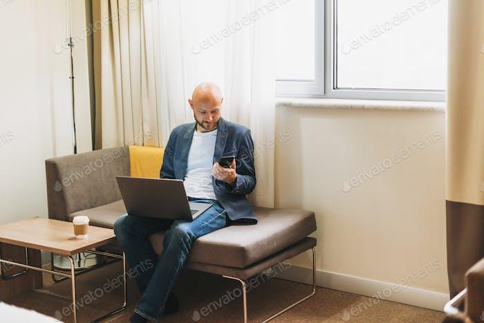 Erwachsene kahlen bärtigen Mann in blauer Jacke mit Kaffee arbeiten auf Laptop im Hotelzimmer