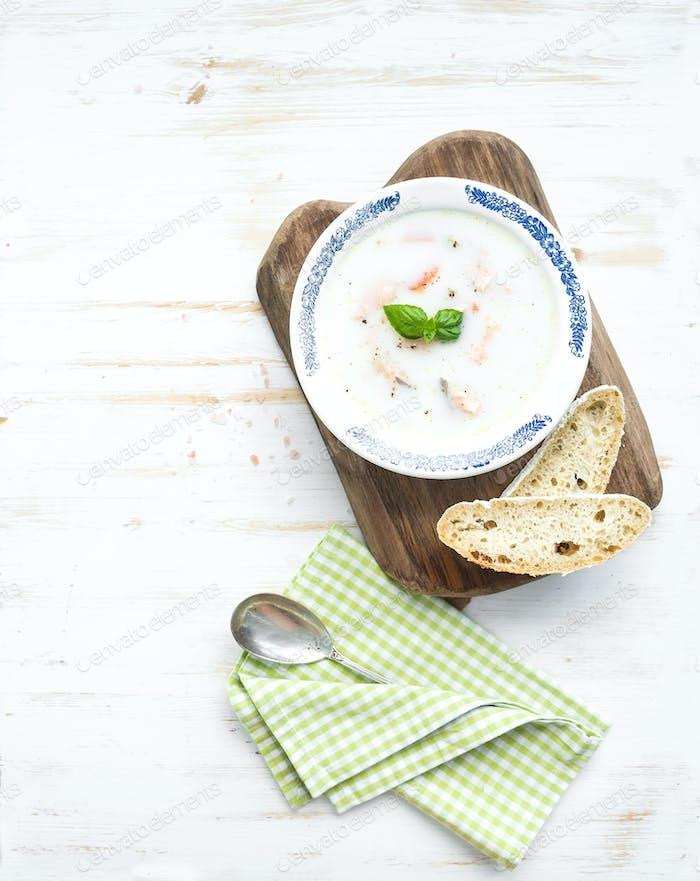 Scandinavian salmon soup with cream, fresh basil and bread