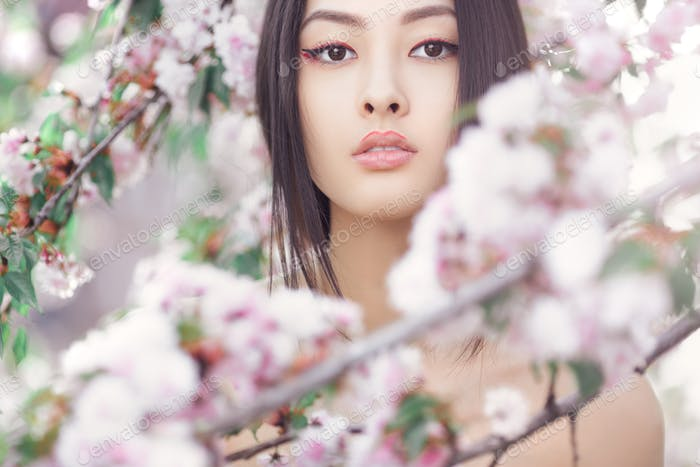 Portrait of a beautiful asian girl outdoors against spring blossom tree