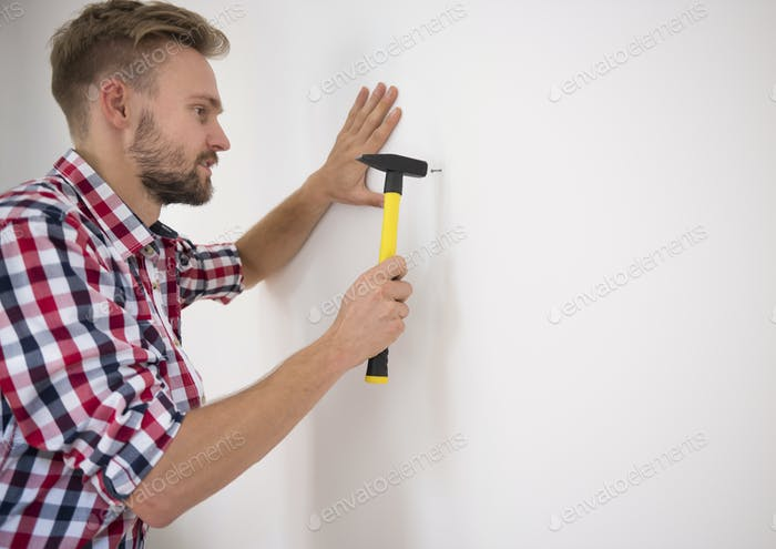 Man hammering a nail into the wall