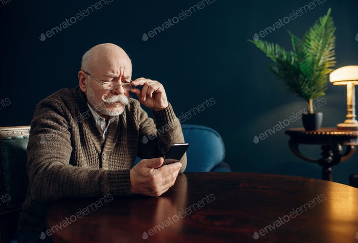 Elderly man using mobile phone in home office