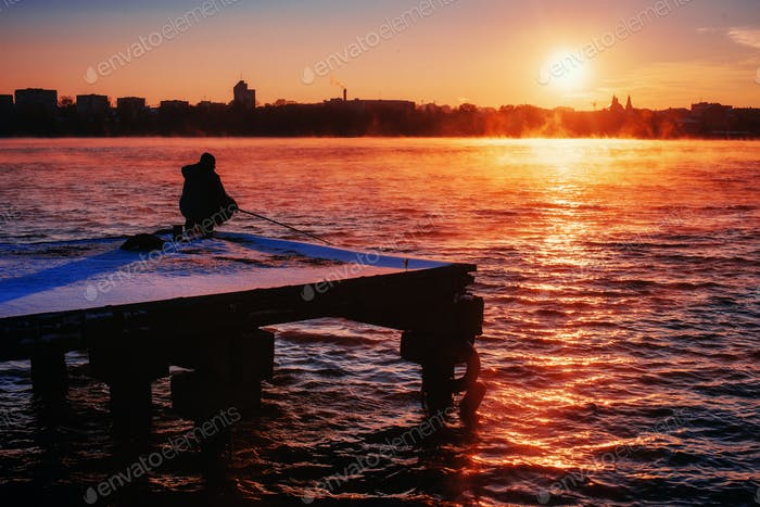 fisherman on the dock at sunset
