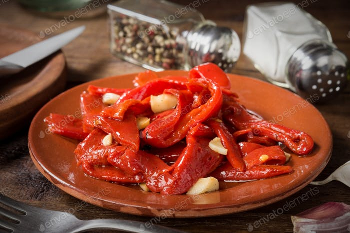 strips of fried red pepper in clay dish on rustic wood