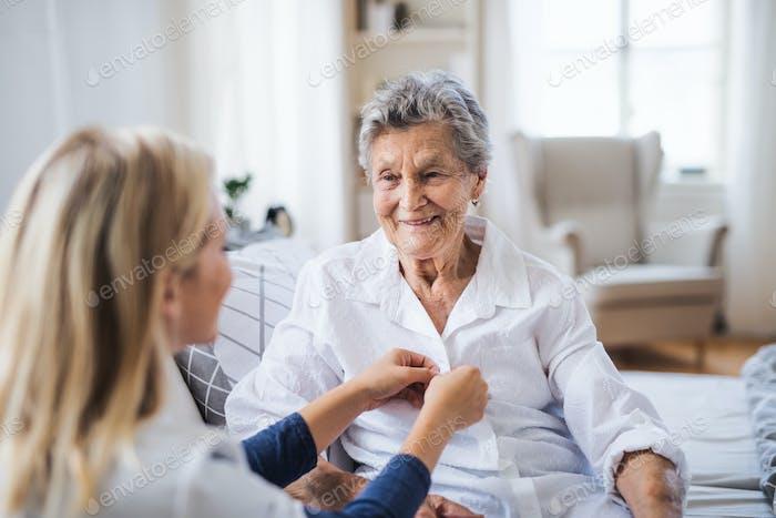 Ein Gesundheitsbesucher hilft einer kranken Seniorin, die zu Hause auf dem Bett sitzt.
