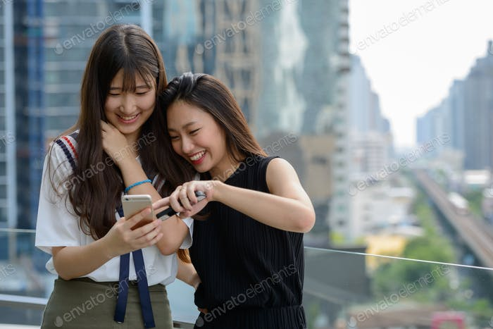 Two happy young beautiful Asian teenage girls using phone together against view of the city
