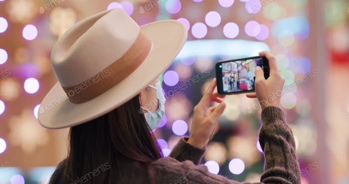 Woman use of mobile phone to take photo with christmas decoration at night