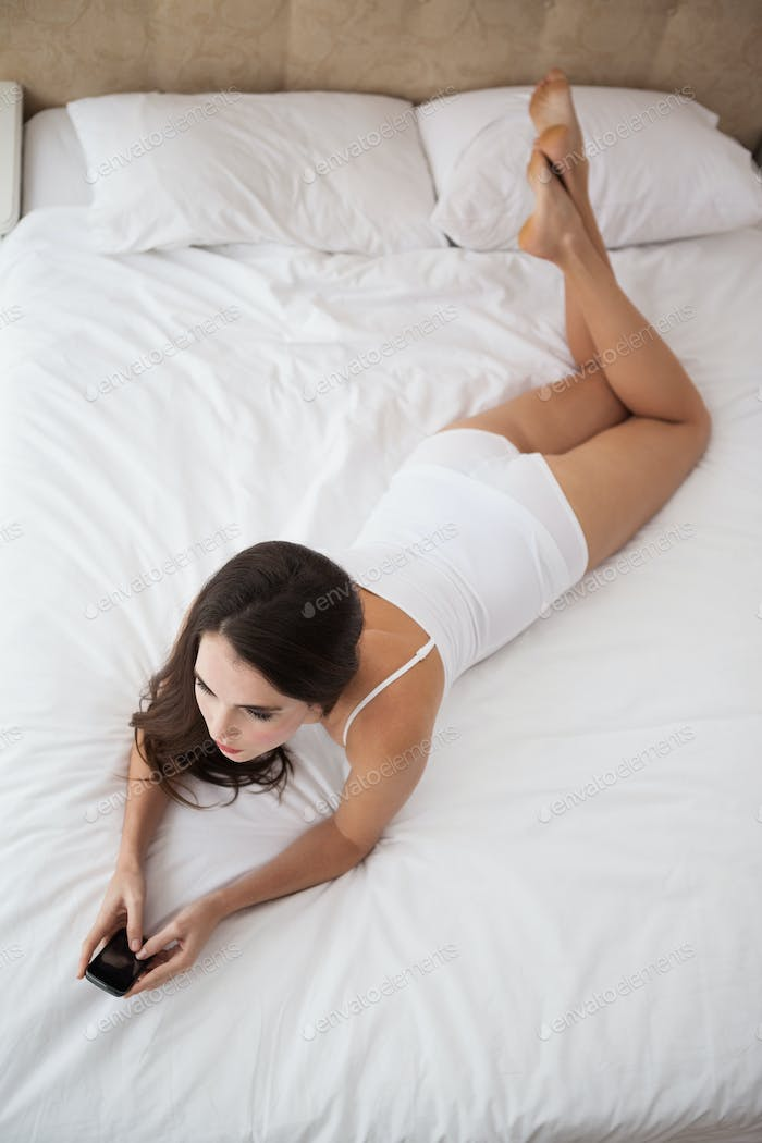 Pretty brunette sending a text on bed at home in the bedroom