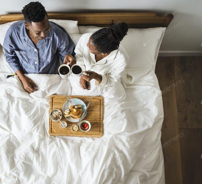Afroamerikanisches Paar im Bett mit Frühstück im Bett