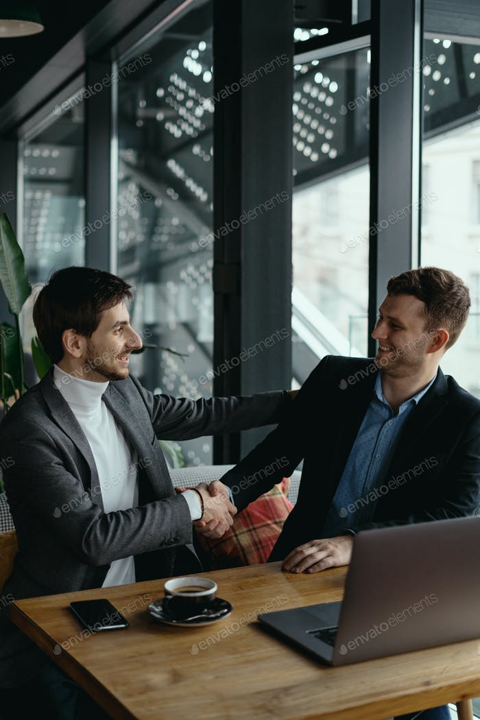 Two businessmen shaking hands while meeting in lobby