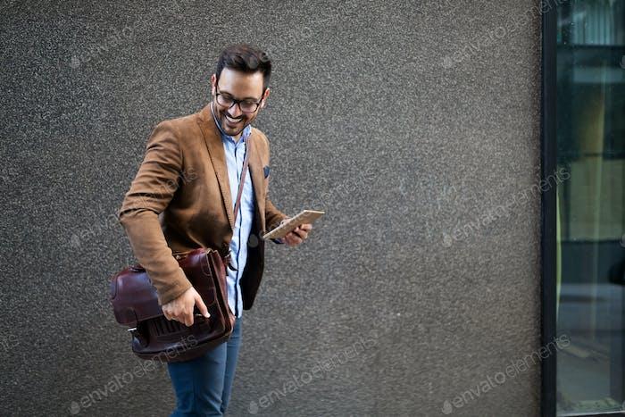Hübsche männliche Marketing-Experten zu Fuß auf der Stadt Straße gehen, um Meeting-Konferenz besuchen